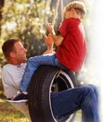 Father and son on tire swing. (Image Credit: Getty Images)